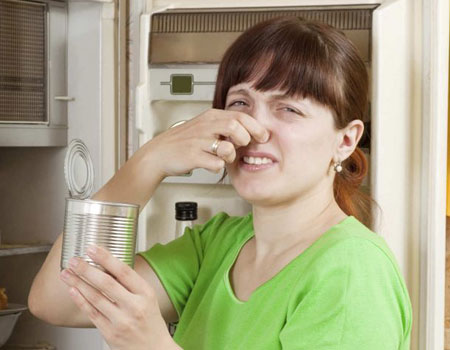 4 Methods to Clear Your House of Tough Odors. woman smelling a bad odor from a can.